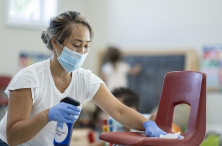 Woman cleaning a chair with a disinfectant