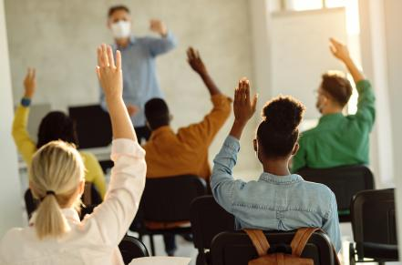 students raising hands in a class